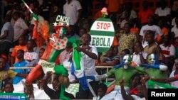 "Penonton berkostum membawa papan bertuliskan ""Stop Ebola"" dalam pertandingan kualifikasi Piala Afrika 2015 antara Pantai Gading dan Sierra Leone di stadion Felix Houphouet Boigny di Abidjan, September 2014. (Reuters/Luc Gnago)"