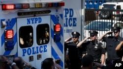 Los compañeros de Brian Moore esperan la salida del cuerpo del hospital Jamaica en Nueva York.