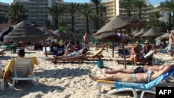FILE - Tourists enjoying the beach near a four-star hotel in the resort town of Sousse, a popular tourist destination south of the Tunisian capital.