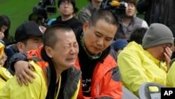 Keluarga korban tenggelamnya kapal ferry Sewol di Jindo, Korea Selatan meratapi anggota keluarga mereka yang tewas atau hilang dalam insiden itu, pada peringatan insiden itu 15 April 2015. Keluarga kembali melancarkan protes bersama demonstran Hari Buruh, 1 Mei 2015.