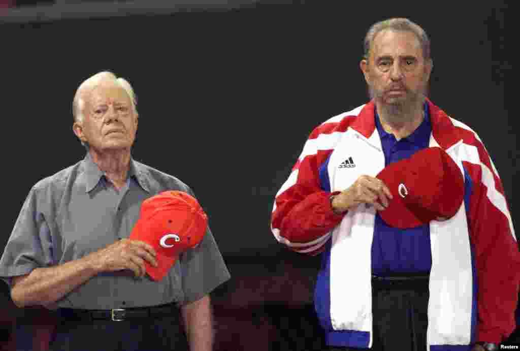 L'ancien président des États-Unis Jimmy Carter et le président cubain Fidel Castro, écoutent l'hymne nationale de Cuba au stade de baseball à La Havane, le 14 mai 2002.