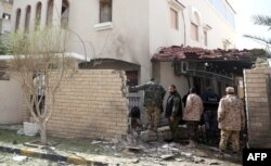 FILE - Libyan security forces inspect the site of a bomb explosion at the entrance of the residence of the Iranian ambassador in the capital Tripoli, Feb. 22, 2015.