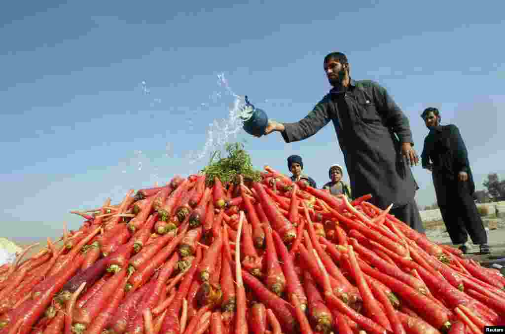 A vendor throws water on a pile of carrots as he waits for customers on the outskirts of Jalalabad city, Pakistan.