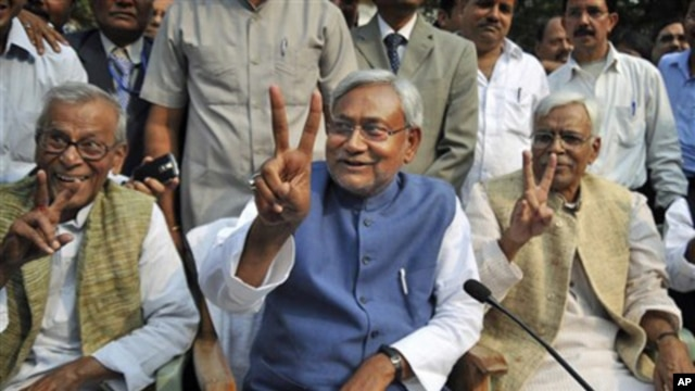 Bihar state Chief Minister Nitish Kumar, center, displays the victory sign during a press conference after his National Democratic Alliance won the state elections, in Patna, India, Nov. 24, 2010. Kumar, the top elected official of one of India's poorest