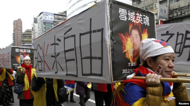 Activists carrying mock-ups of coffins to mourn for those who killed themselves in self-immolation, take part in a rally to commemorate the uprising in Lhasa 53 years ago against Chinese rule, March 10, 2012.