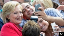 Democratic presidential candidate Hillary Rodham Clinton poses for a photo with two of her supporters on the campus of Case Western Reserve University in Cleveland.