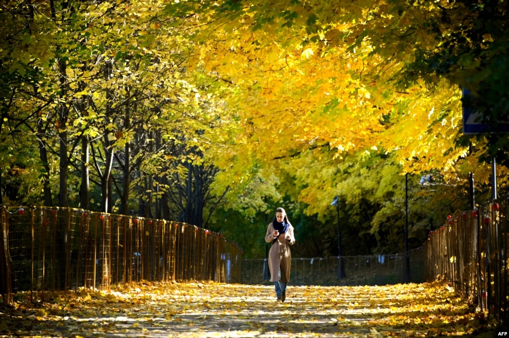 A woman walks in a park at Vorobyovy Hills in Moscow, Russia.