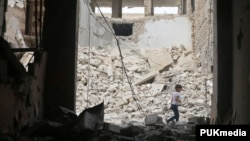 A child walks past damaged buildings after an airstrike in the rebel-held area of Aleppo's Baedeen district, Syria, May 3, 2016.