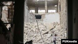 在叙利亚阿勒颇反政府组织控制的地区一名儿童在空袭后走过房屋废墟 (2016年5月3日)