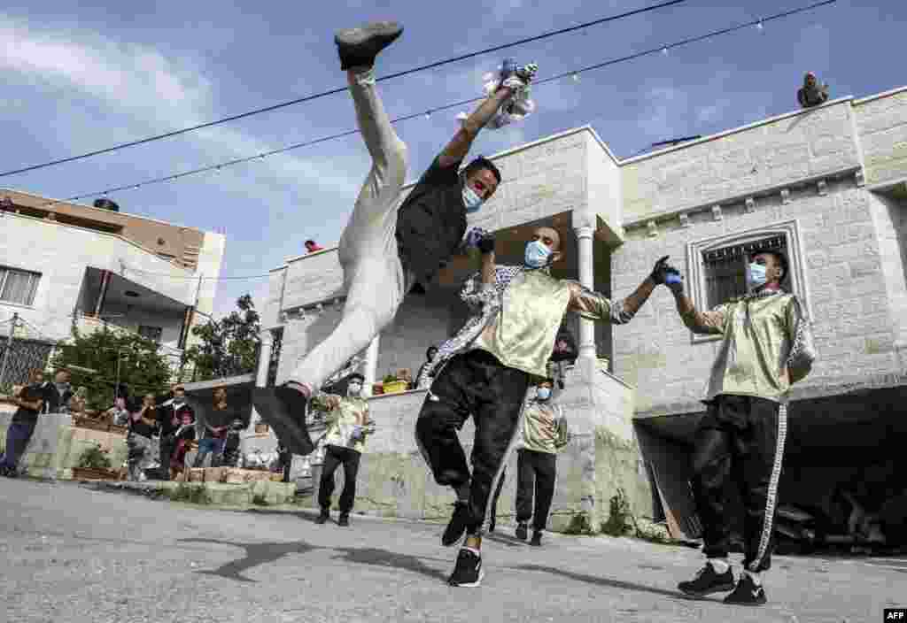 Dancers of the Palestinian Jafra Dabke Team perform a traditional dabke dance during a COVID-19 coronavirus pandemic lockdown in the village of Tarqumia northwest of Hebron in the occupied West Bank.