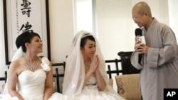 Huang Mei-yu (kiri) dan pasangannya You Ya-ting disambut oleh Biksuni Shih Chao-hui sebelum upacara pernikahan sebagai pasangan lesbian pertama yang dinikahkan dalam pemberkatan Budha di Taoyuan, Taiwan (11/8).