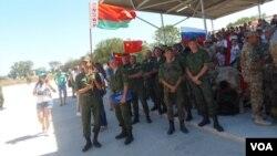 8月份俄罗斯举办国际军事比赛活动,在南部叶伊斯克市防空部队比赛中手举国旗的白俄罗斯军队士兵。后面是俄罗斯和中国国旗。