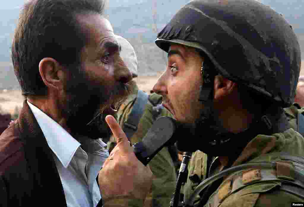 A Palestinian man argues with an Israeli soldier during clashes over an Israeli order to shut down a Palestinian school near Nablus in the occupied West Bank.
