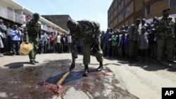Kenyan police officers clean the scene where a police van was attacked at the Eastleigh neighbourhood in the capital Nairobi, 03 Dec 2010
