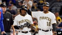 Pittsburgh Pirates' Gift Ngoepe, a native of South Africa, and the first baseball player from the continent of Africa to play in the Major Leagues celebrates with first base coach Kimera Bartee (18) after getting a single off Chicago Cubs starting pitcher