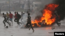 People run at a protest as barricades burn during rainfall in Harare