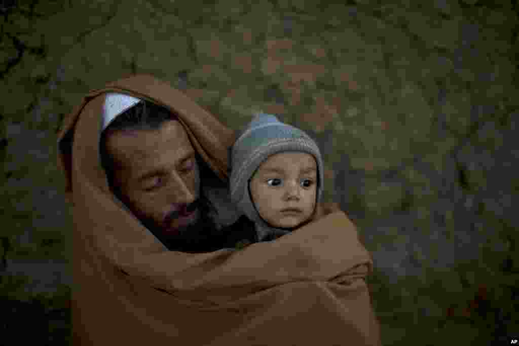 Pakistani Ibrahim Mohammed, 42, who was displaced with his family from Pakistan's tribal region of Mohmand Agency due to fighting between the Taliban and the army, wraps himself and his son Mashal, 1, with a shawl to avoid the evening cold, while sitting in front of his home in a poor neighborhood on the outskirts of Islamabad.