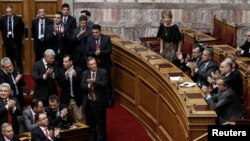 PM Yunani Antonis Samaras (kanan) dan para pembuat kebijakan pemerintah Yunani memberikan tepuk tanganseusai pelaksanaan putaran ketiga pemilu Presiden di Parlemen Yunani, Athena (23/12).