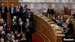 Greece's Prime Minister Antonis Samaras (R) and lawmakers of the government applaud after the second of three rounds of a presidential vote at the Greek parliament in Athens, Dec. 23, 2014.