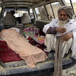 An elderly Afghan man sits in a minivan next to the covered body of a person allegedly shot dead by a U.S. service member in Panjwai, Kandahar province, Afghanistan, March 11, 2012.