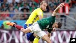 El sueco Andreas Granqvist y el mexicano Javier Hernandez, (frente) durante el partido por que México perdió 3-0 frente a Suecia.