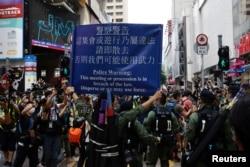 香港警察对在中国国庆日要求北京政府释放12港人的抗议者展示警示牌。(2020年10月1日)