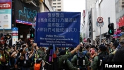 资料照:香港警察对在中国国庆日要求北京政府释放12港人的抗议者展示警示牌。(2020年10月1日)