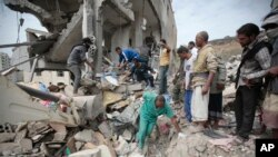People inspect the rubble of houses destroyed by Saudi-led airstrikes in Sanaa, Yemen, on Friday, Aug. 25, 2017.