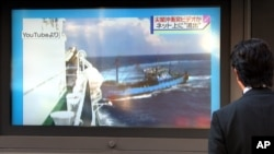 FILE - A man watches a TV news showing a YouTube video which is said to be showing a collision between a Chinese fishing boat, right, and a Japanese coast guard vessel off disputed islands in Tokyo.