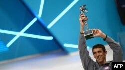 Perenang AS, Michael Phelps mengangkat piala Atlet Terbaik Olimpiade Sepanjang Masa yang diperolehnya setelah memenangkan medali emas dalam nomor final pertandingan renang putra 4x100m medley di Olimpiade London 2012 (4/8).