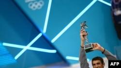 US swimmer Michael Phelps poses after receiving the trophy of the greatest olympic athlete of all time after winning gold in the men's 4x100m medley relay final during the swimming event at the London 2012 Olympic Games on August 4, 2012 in London.