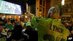 Stunned Seattle Seahawks fan Dustin Pittis points at a TV monitor, Feb. 1, 2015, as he watches the end of Super Bowl XLIX at a bar in Seattle, Washington.
