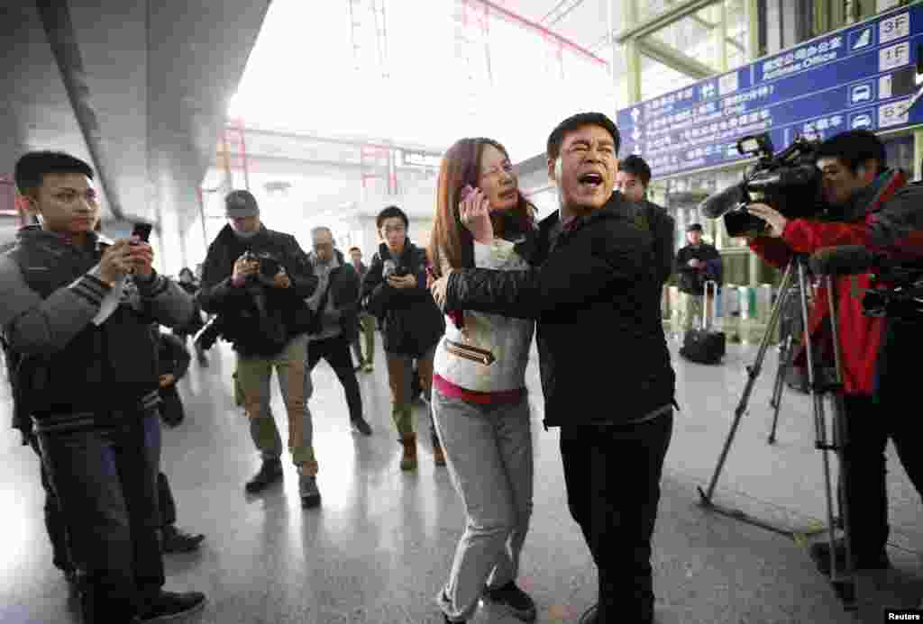 A relative of a passenger onboard Malaysia Airlines flight MH370 cries as she talks on her mobile phone at the Beijing Capital International Airport in Beijing, China. The Malaysia Airlines flight carrying 227 passengers and 12 crew lost contact with air traffic controllers en route from Kuala Lumpur to Beijing, the airline said in a statement.