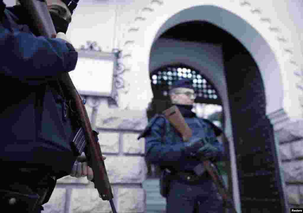 Polisi Perancis berjaga-jaga di depan pintu masuk Masjid Agung Paris sebagai bagian langkah keamanan tingkat tertinggi menyusul serangan militan Islamis minggu lalu di Paris (14/1).(Reuters/Christian Hartmann)