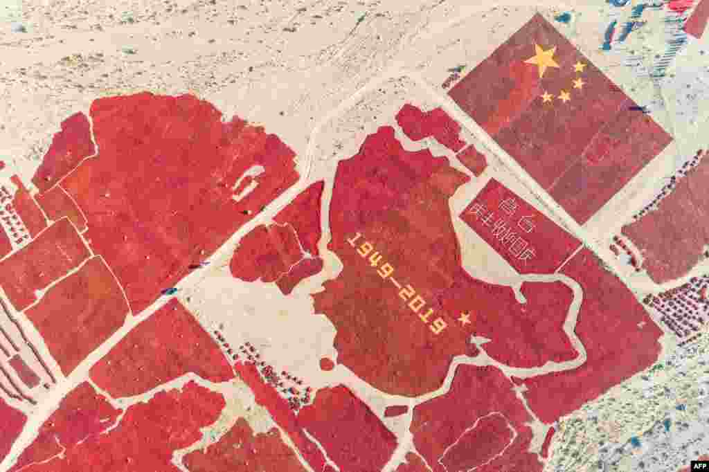 This aerial photo shows the image of a Chinese map and a national flag formed by dried chili peppers during the harvest season in Zhangye in China's northwestern Gansu province, as farmers celebrate the 70th anniversary of the founding of the People's Republic of China.