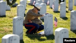 FILE - A female U.S. Marine touches the grave of a friend at Arlington National Cemetery in Virginia. The Veterans Day holiday dates back to 1919.
