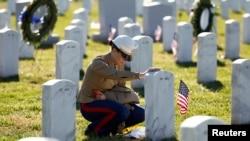 Seorang anggota marinir AS memberikan penghormatan dengan menyentuh batu nisan pada makam rekannya yang dimakamkan di Taman Makam Pahlawan di Arlington, Virginia (Foto: dok).