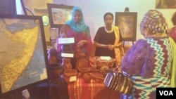 Nathifa Hashi, left, from Somalia explains items used by nomads in an exhibit at an Africa Day gala in Washington, May 27, 2016.