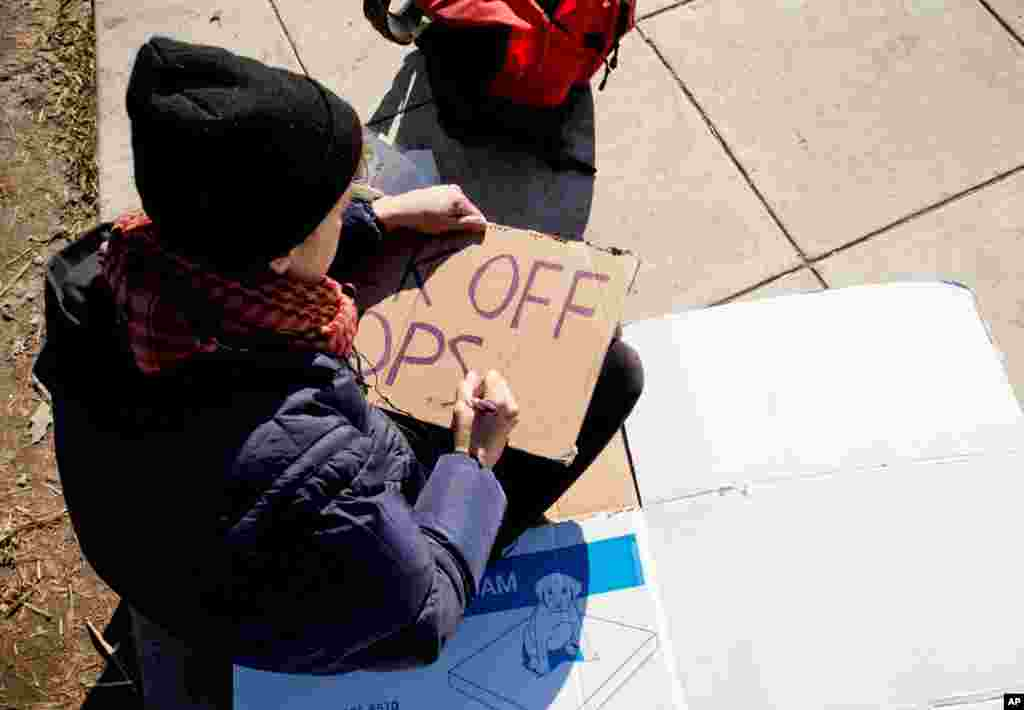"An Occupy DC participant makes a sign that reads ""Back Off Cops"" in McPherson Square in Washington, Monday, Jan. 30, 2012, in preparation of enforcement of no-camping regulations. (Alison Klein/VOA)"