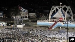 People attend a mass celebrated by Pope Benedict XVI in Antonio Maceo square in Santiago, Cuba, March 26, 2012.