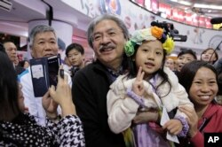 Chief Executive candidate, Hong Kong's former Financial Secretary John Tsang Chun-wah, center, holds a child as he poses for a photograph with his supporters at a election campaign in Hong Kong, March 16, 2017.