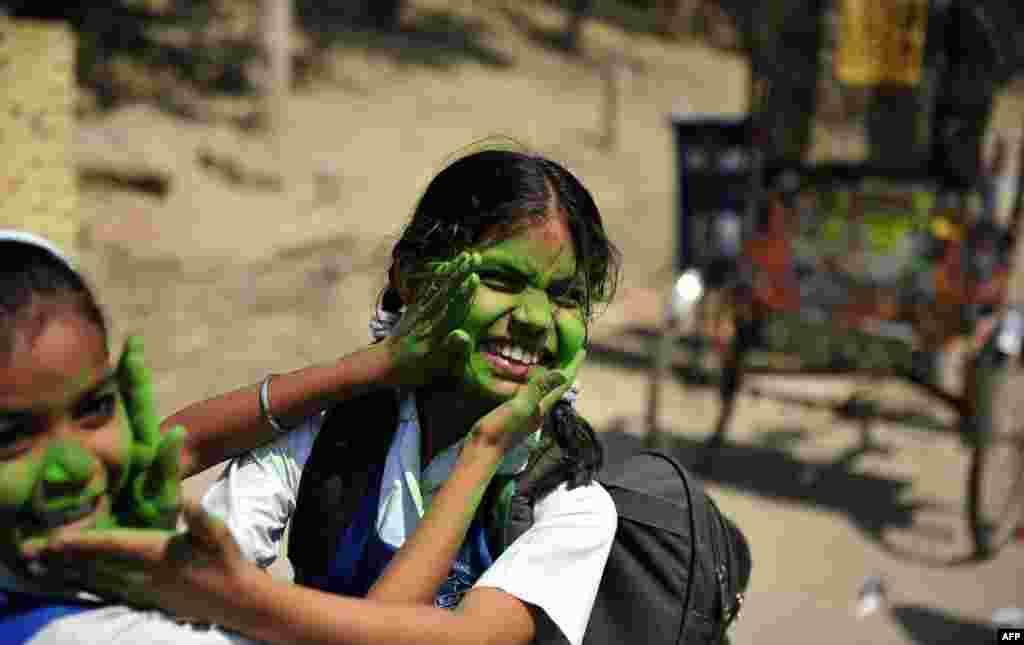 Dvije učenice, Indijke, iskušavaju boju kojom će za Holi, prvi dan tradicionalni proljetnog festivala Hindusa (ove godine počinje 27. marta) premazati lica.