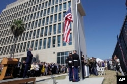 FILE - U.S. Secretary of State John Kerry watches the raising of the American flag at the newly opened U.S. Embassy in Havana, Cuba, Aug. 14, 2015.