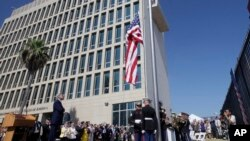 FILE - Officials watch the raising of the American flag at the newly opened U.S. Embassy in Havana, Cuba, Aug. 14, 2015.