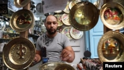 FILE - An artisan works on bronze plates in the Medina, in the old city of Tunis, Tunisia September 14, 2019. (REUTERS/Muhammad Hamed)