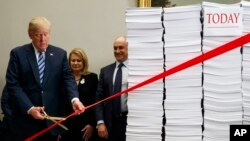 "President Donald Trump cuts a ceremonial red tape during an event on federal regulations at the White House, Dec. 14, 2017, in Washington. ""Let's cut the red tape, let's set free our dreams,"" Trump said, next to stacks of paper that he said represented the size of the federal regulatory code."