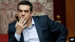 Greece's Prime Minister Alexis Tsipras gestures during a parliamentary session in Athens, March 30, 2015, after Tsipras called the special session of parliament to brief lawmakers on the course of recent troubled negotiations with bailout lenders to overhaul cost-cutting reforms.