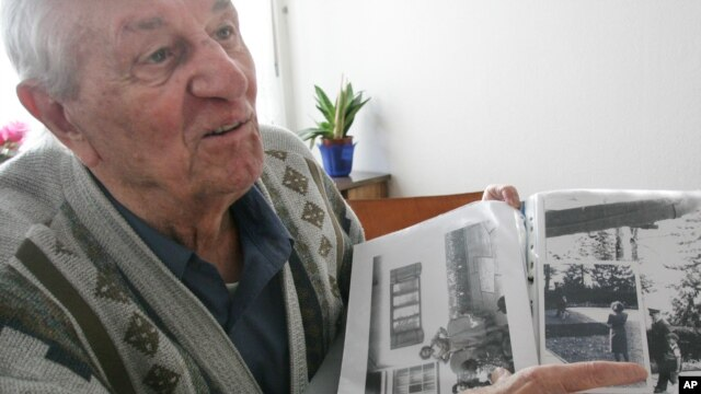 In this 2005 file photo Hitler's bodyguard, Rochus Misch, points on a picture of Adolf Hitler he had taken in Berchtesgarden, southern Germany.