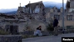 Warga berdiri di pinggir jalan menyusul gempa yang melanda kota Amatrice, Italia tengah (24/8). (Reuters/Emiliano Grillotti)