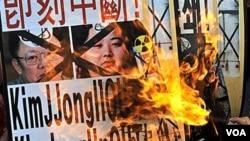 Warga Korsel membakar poster pemimpin Korut Kim Jong-il dan Kim Jong-un dalam protes di Seoul, 28 Desember 2010.